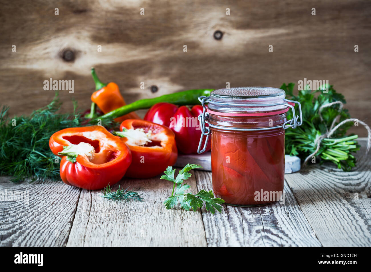 Homemade  pickled peppers in tomato juice and sweet bell red pepper on rustic table Stock Photo