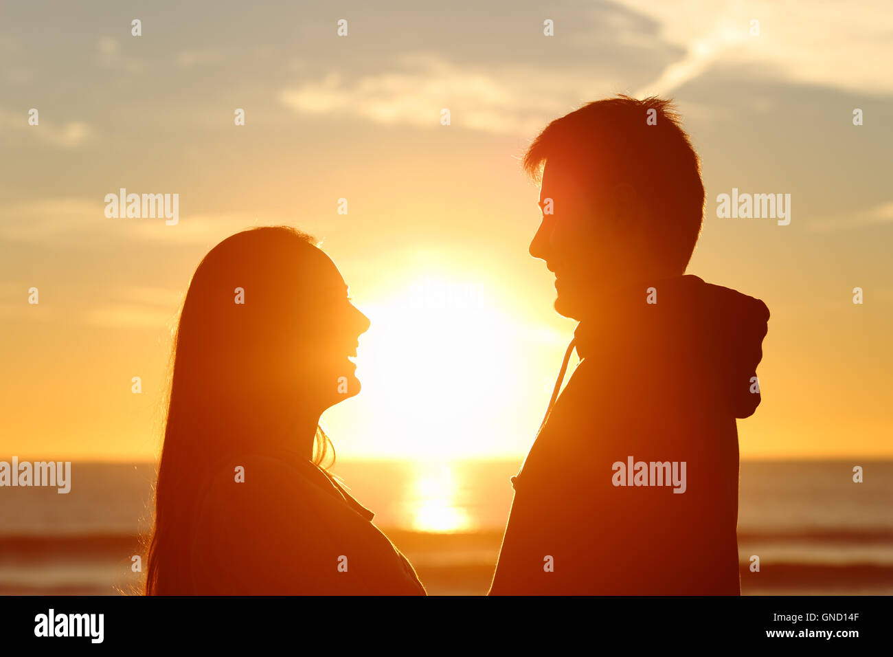 Couple standing looking each other and falling in love with the sun in the middle at sunset in the beach - Stock Image