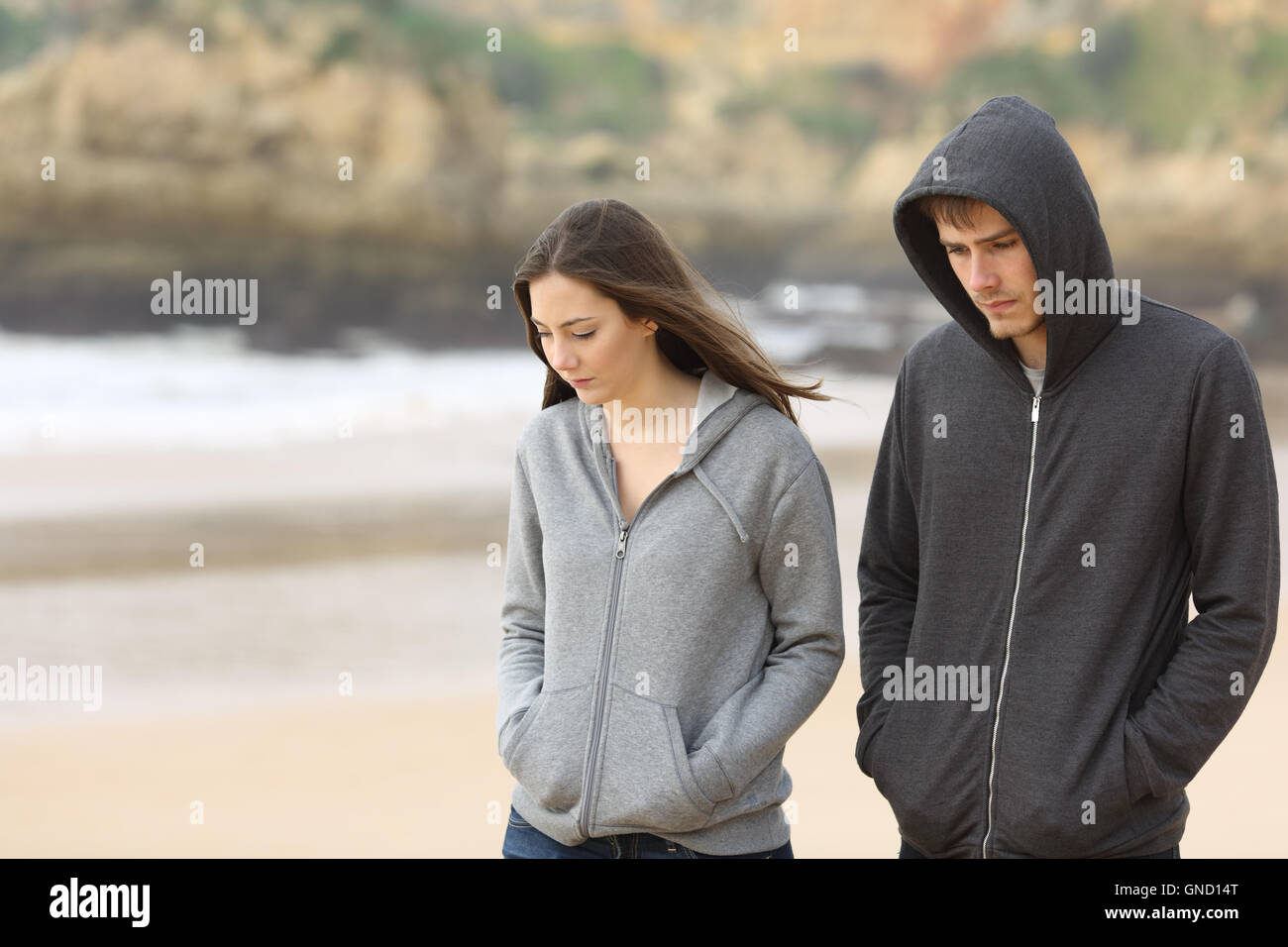 Couple of angry and sad teenagers together walking on the beach - Stock Image