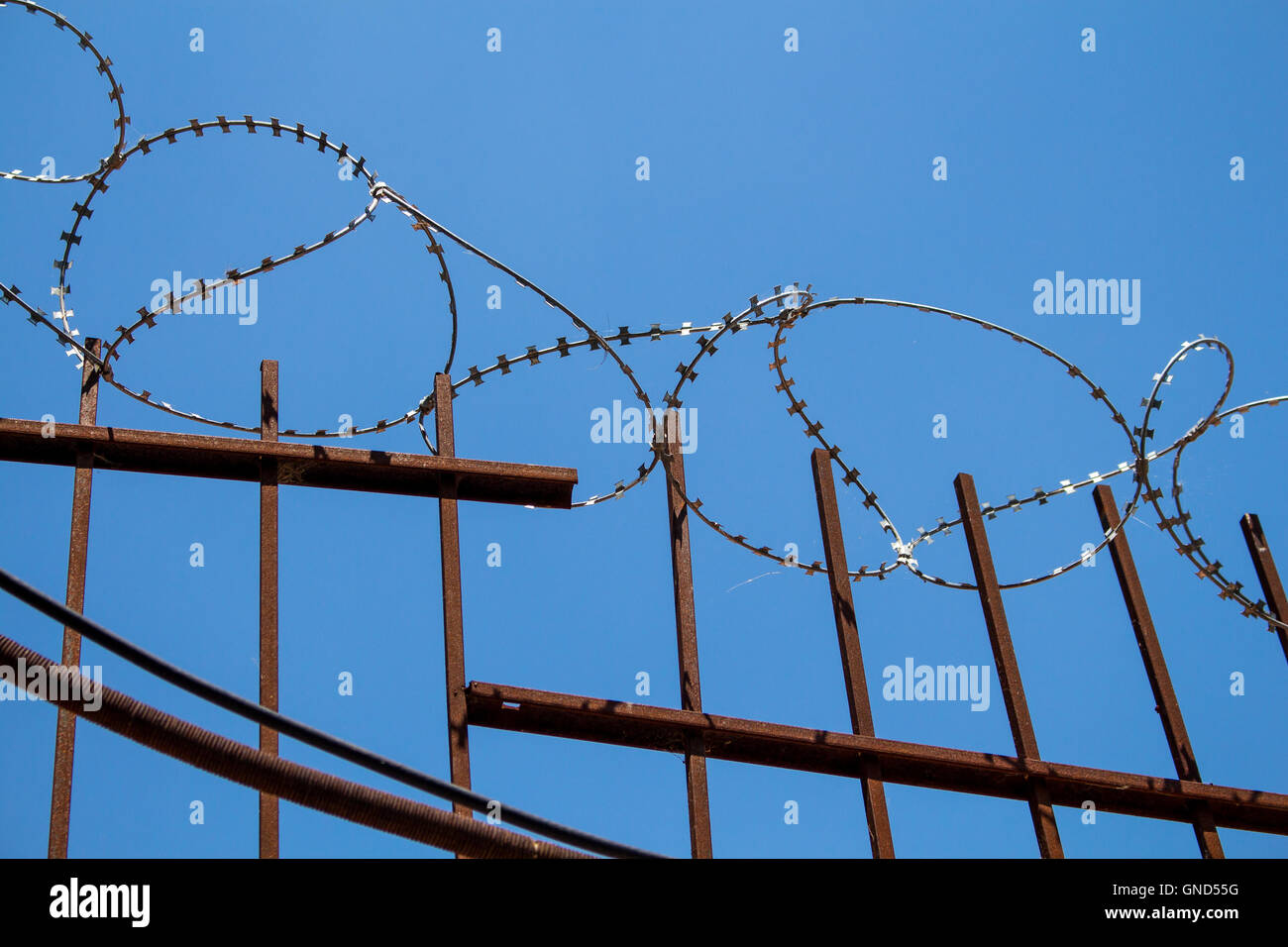 Enlightened barbed wire on the top of a metal fence. Bright blue sky in the background. - Stock Image