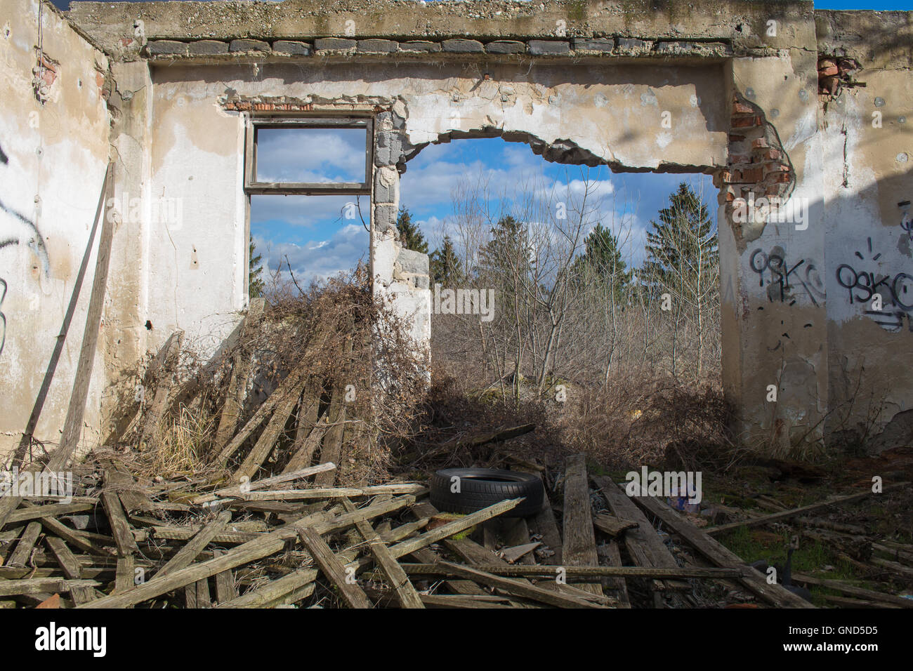 View from the room of an abandoned house, with a broken wall, showing the trees and cloudy sky outside. - Stock Image