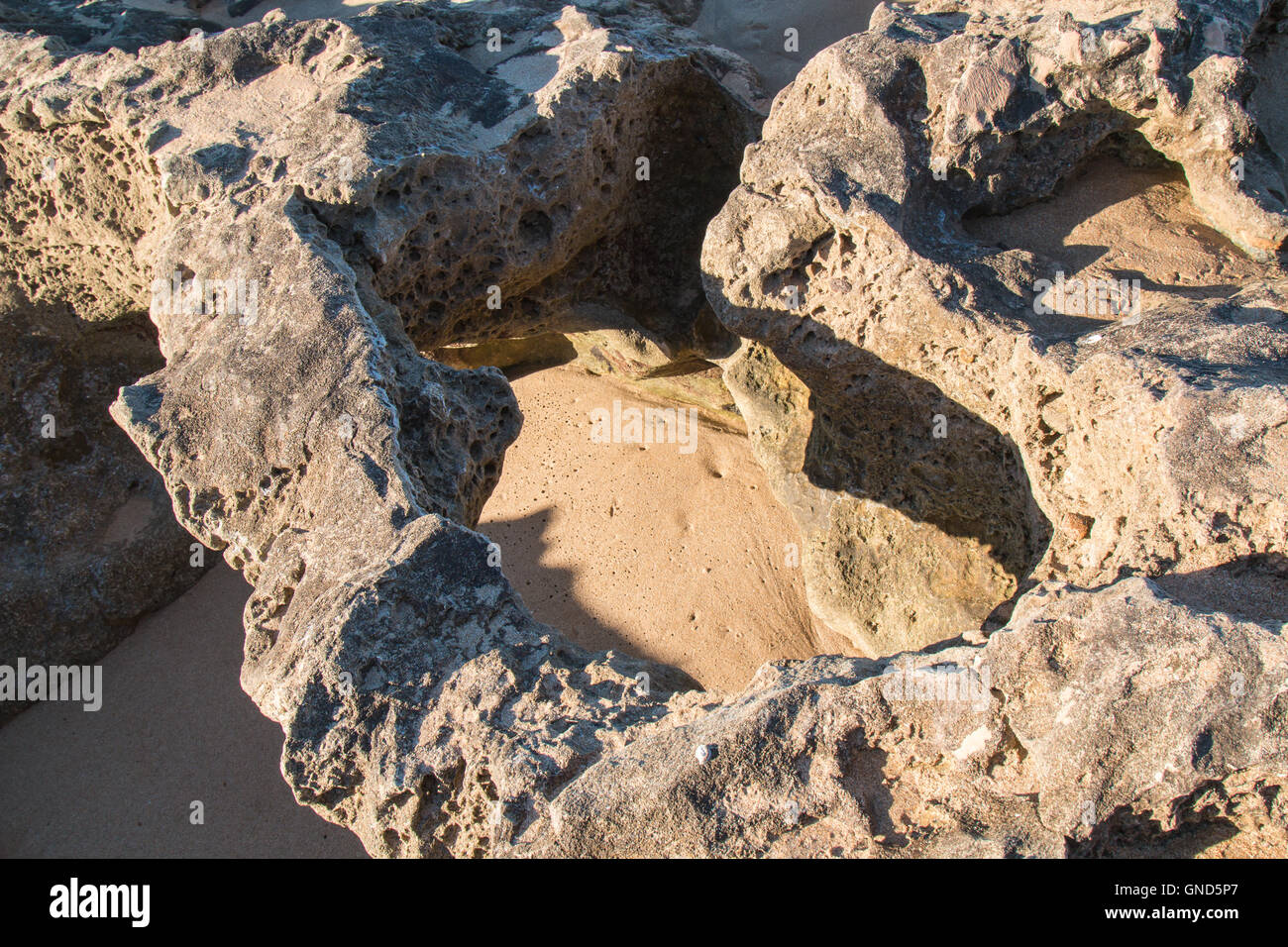 Rocks with sharp edges and holes on the beach of Atlantic Ocean in Morocco during the low tide. Enlightened hole - Stock Image