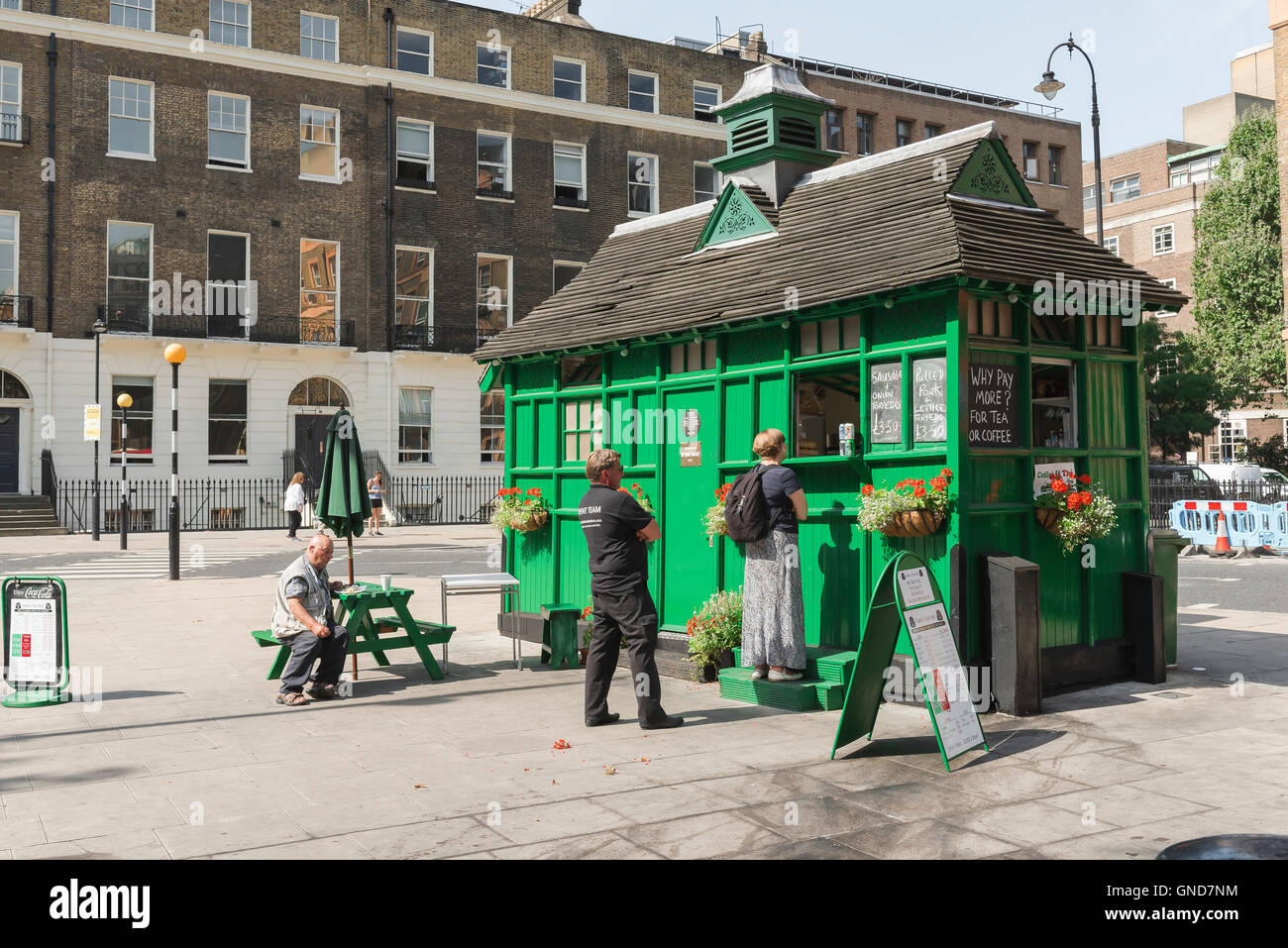 London street food, people buy cooked food from a converted cabmen's shelter in Russell Square, Bloomsbury, - Stock Image