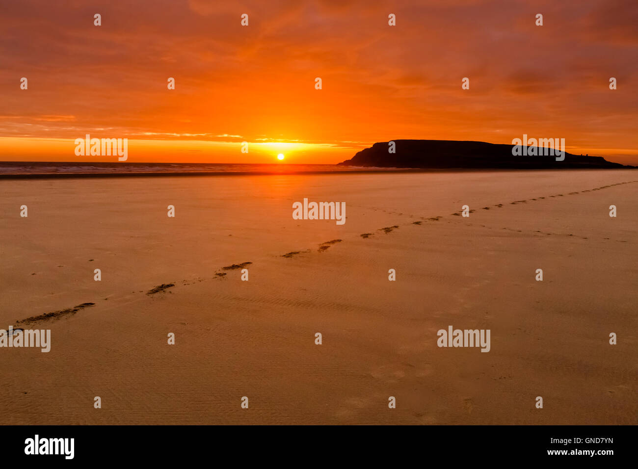 Sun setting behind Burry Holms, from Rhossili Beach. Stock Photo