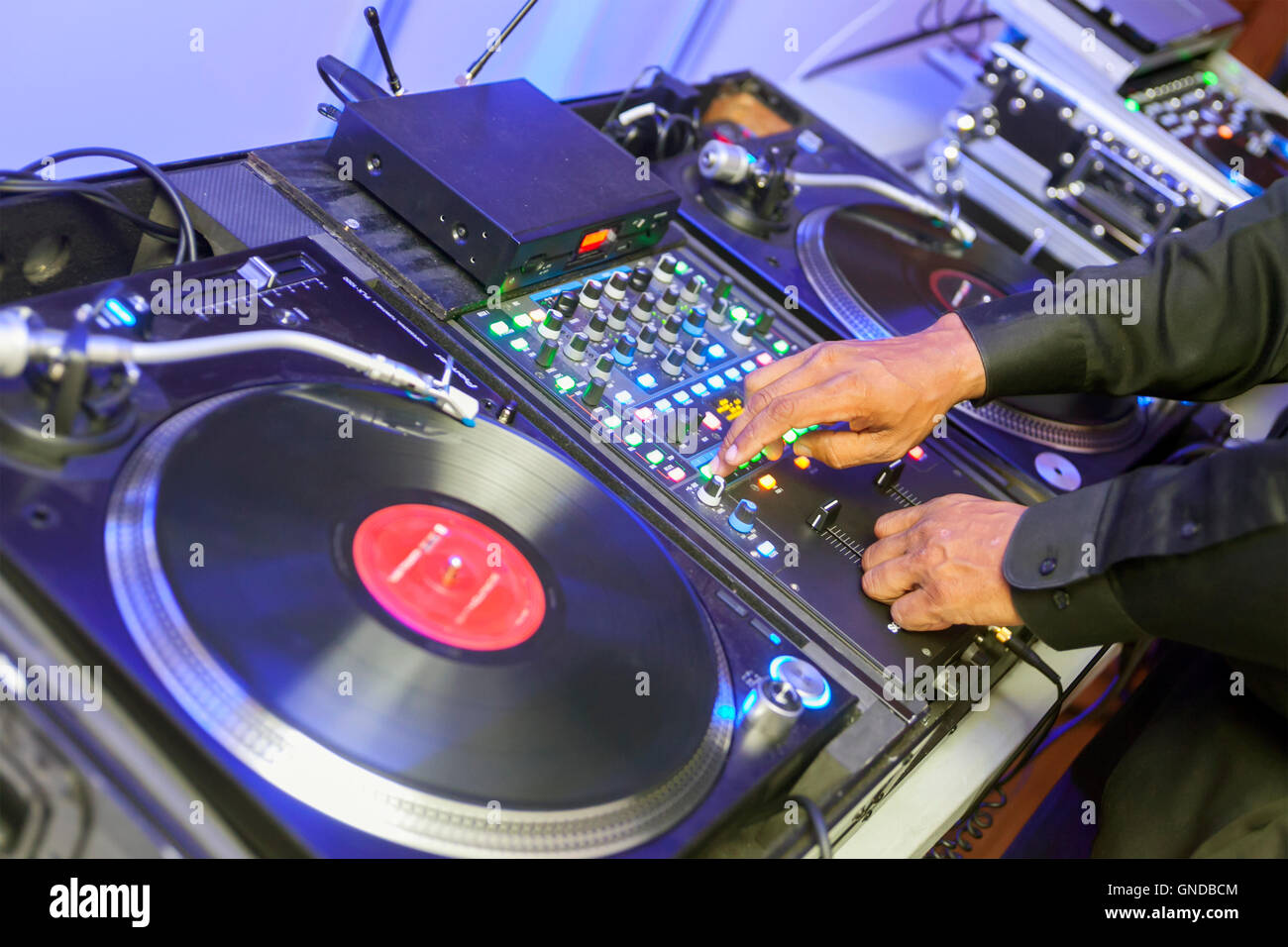 The DJ, Disc Jockey, plays vinyl records and music for a party. - Stock Image