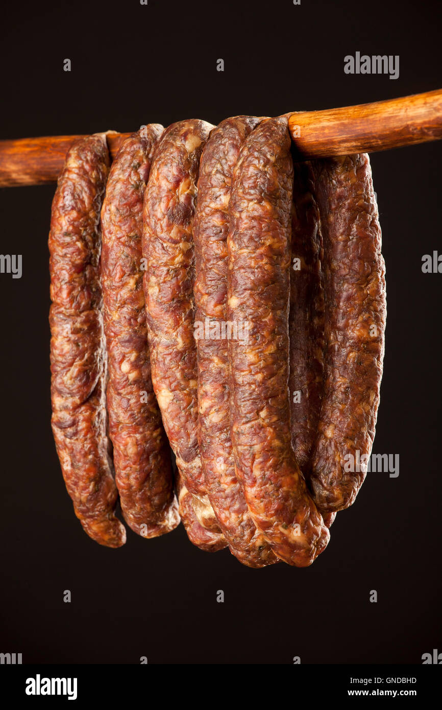 hanging smoked sausage on a stick on black background - Stock Image