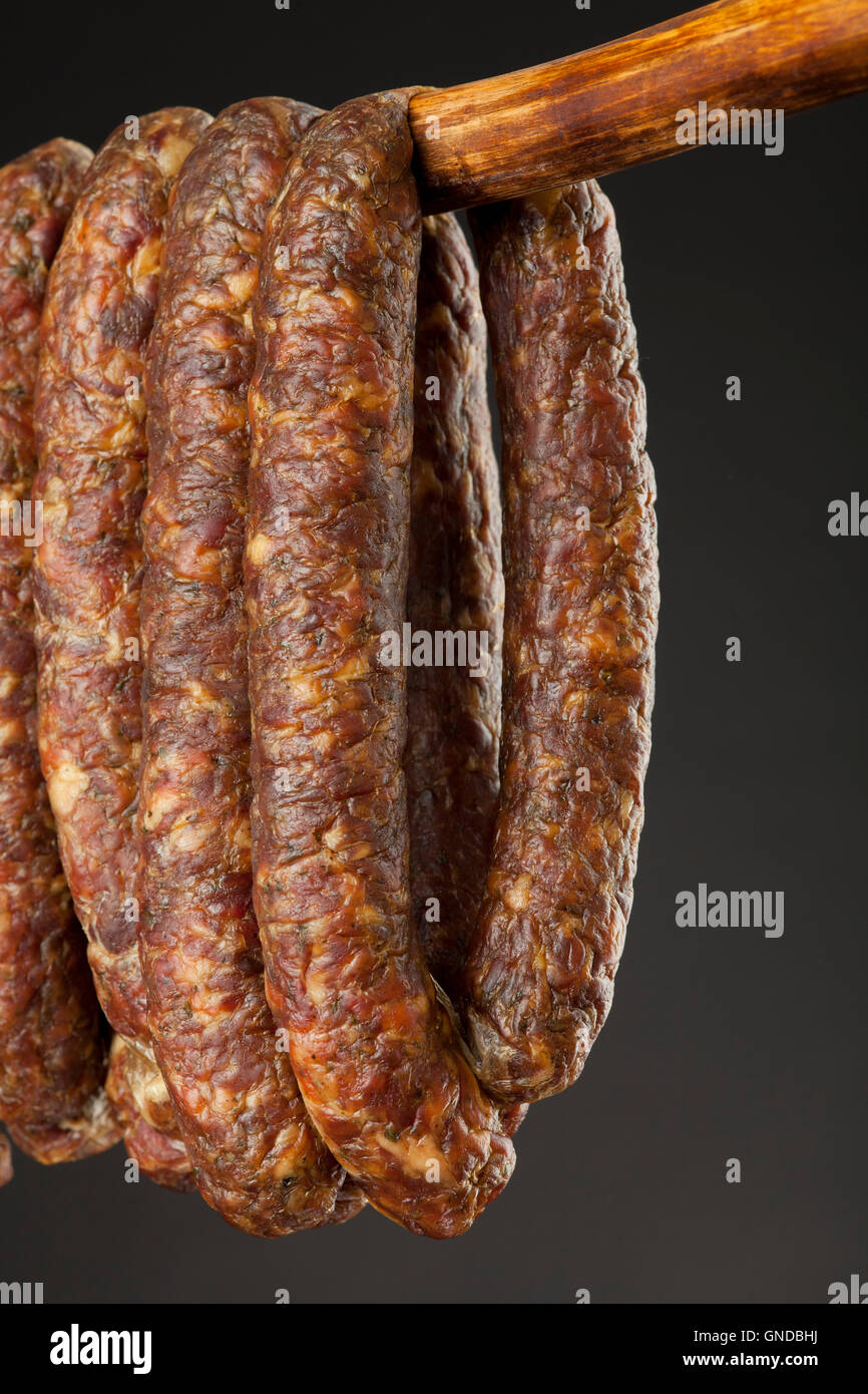 hanging smoked traditional sausage on a stick on black background - Stock Image
