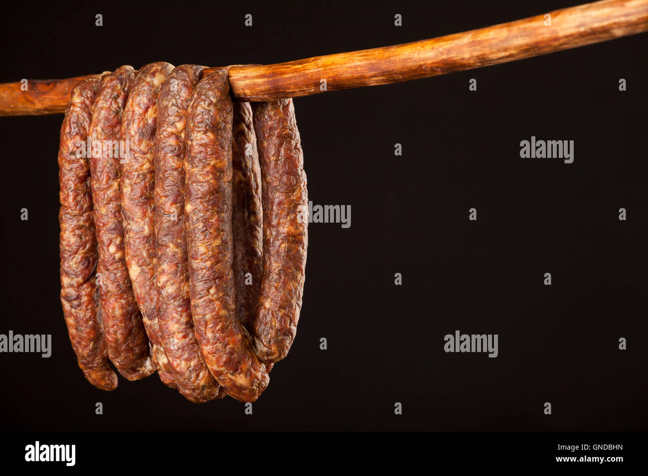 hanging smoked domestic traditional sausage on a stick on black background - Stock Image