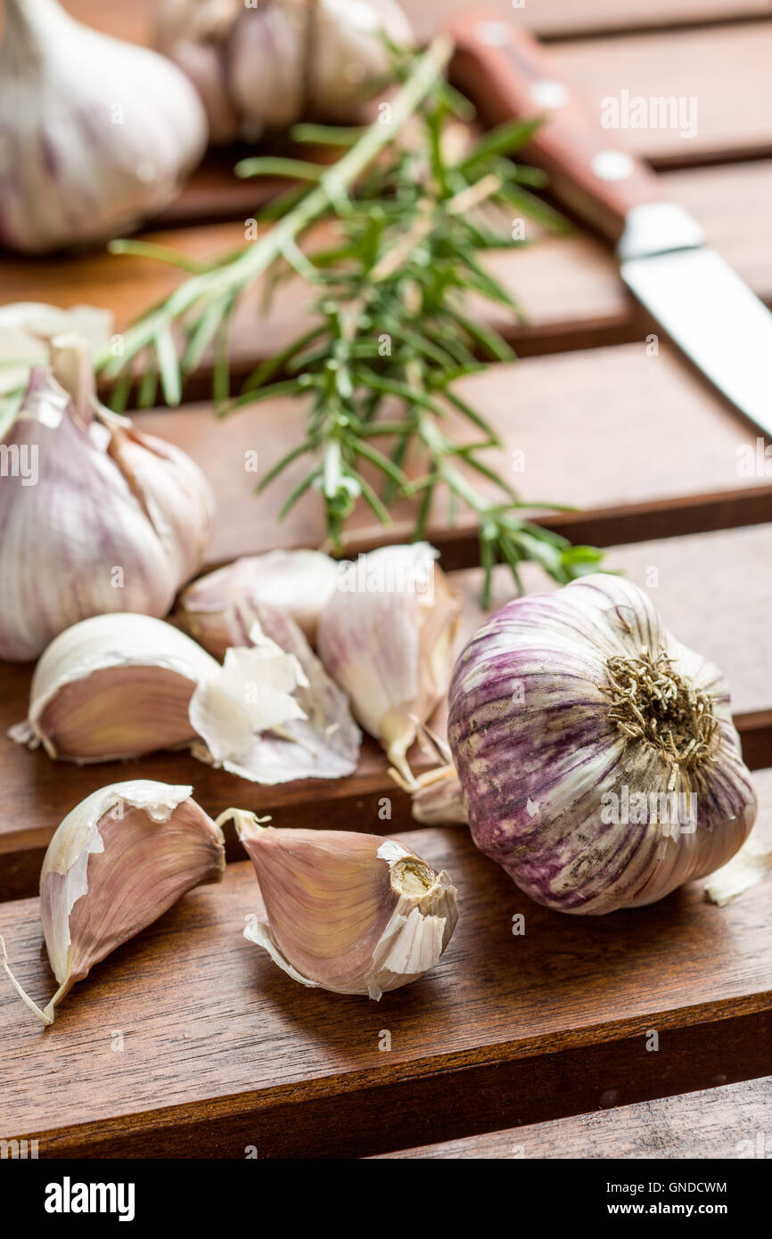 Garlic and rosemary on wooden table. - Stock Image