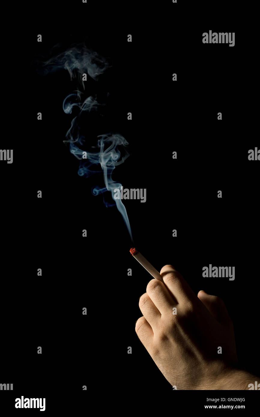 hand holding a smoking cigarette isolated - Stock Image
