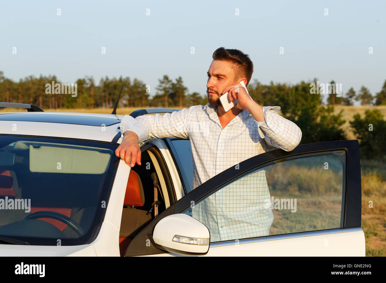 Young handsome man opened the door of his car. Man speaks by phone. Always connected. - Stock Image