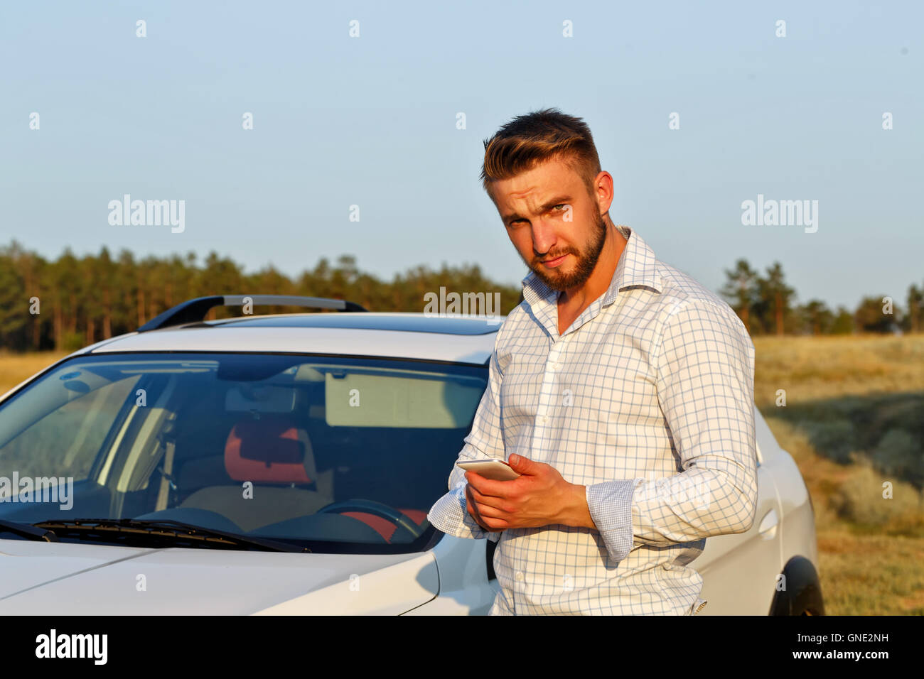 A young handsome man standing in front of the car. A man holding a smartphone. Always connected. - Stock Image