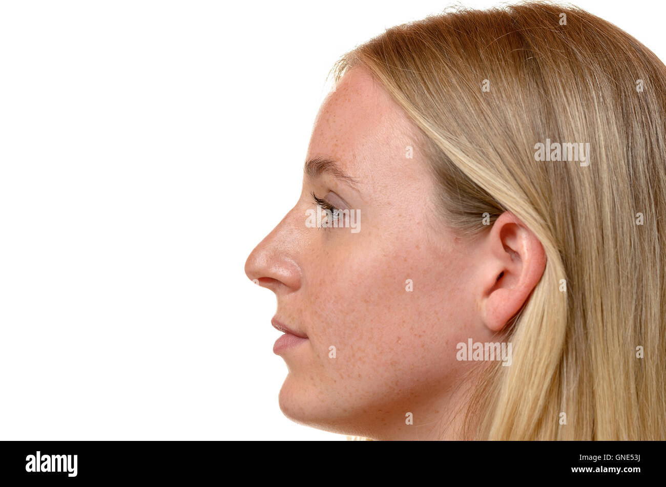 Side profile view of the face of an attractive blond woman with her long hair tucked behind her ear isolated on - Stock Image