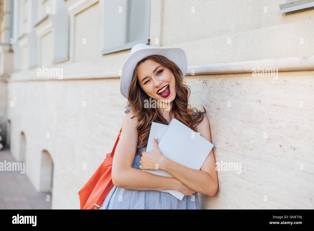 Cheerful pretty young woman in hat with blank covered magazines winking and showing thumbs up Stock Photo