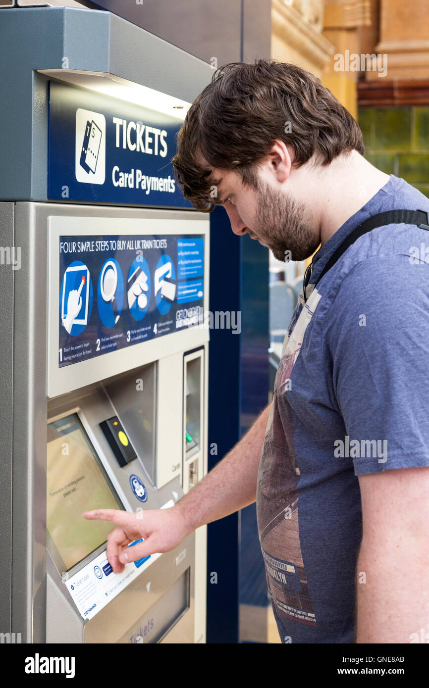 Man buying train tickets at a ticket machine, Nottingham ...
