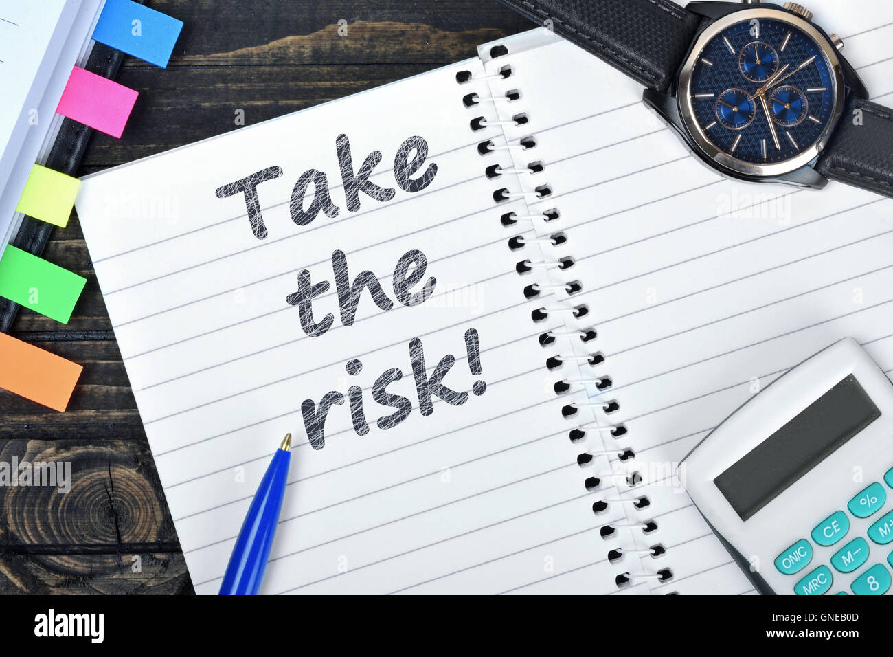 Take the risk text on notepad and watch on desk - Stock Image