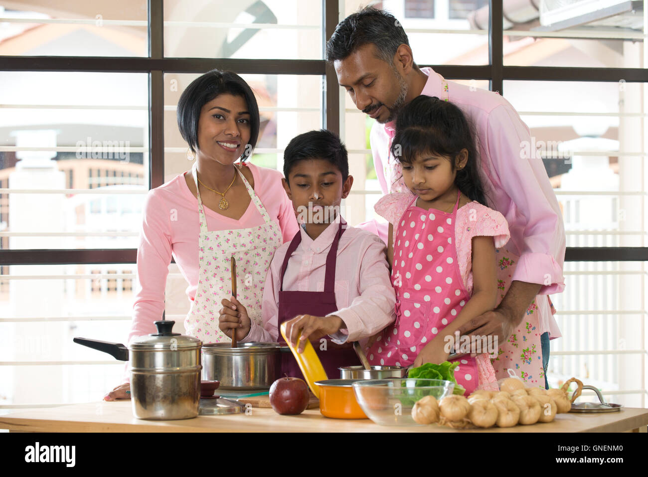 Indian Family Spending Quality Time Busy Cooking At Home Stock Photo