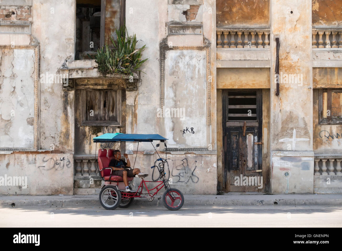 A man rests sitting on his bicitaxi in front of a decrepit abandoned building. Havana, Cuba. - Stock Image