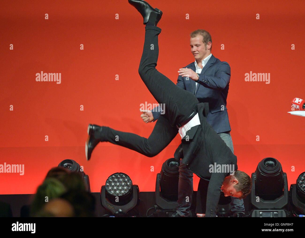 Gold medalist Fabian Hambuechen lets presenter Alexander Bommes show a handstand at the Sport Bild-Award ceremony Stock Photo