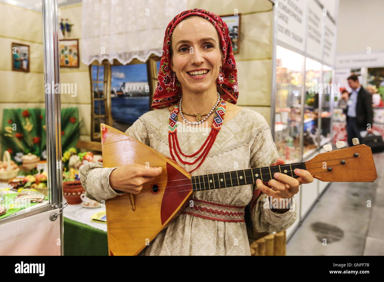 ST PETERSBURG, RUSSIA - AUGUST 30, 2016: A woman in a national costume plays the balalaika at the 2016 Agrorus international - Stock Image