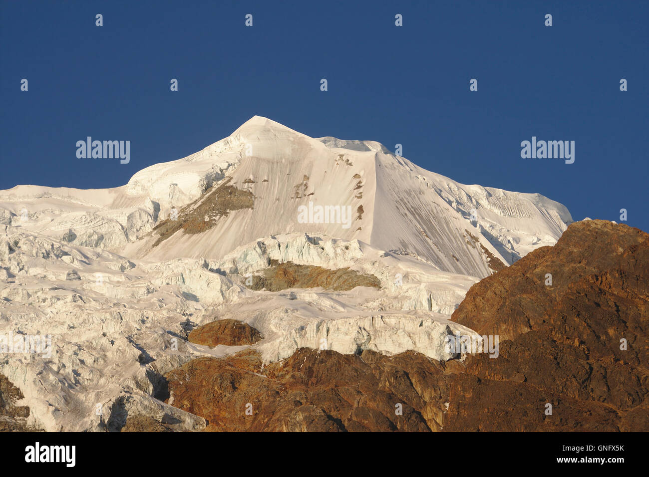 Illimani (side peak) from Base Camp in evening light, Cordillera Real, Bolivia - Stock Image