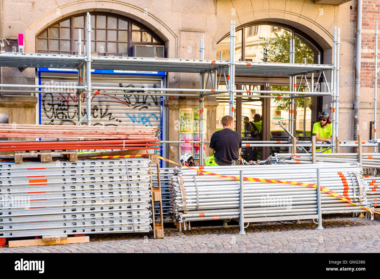 Lund, Sweden - August 24, 2016: Two male scaffolding builders taking a break during the day. Piles of metal poles - Stock Image