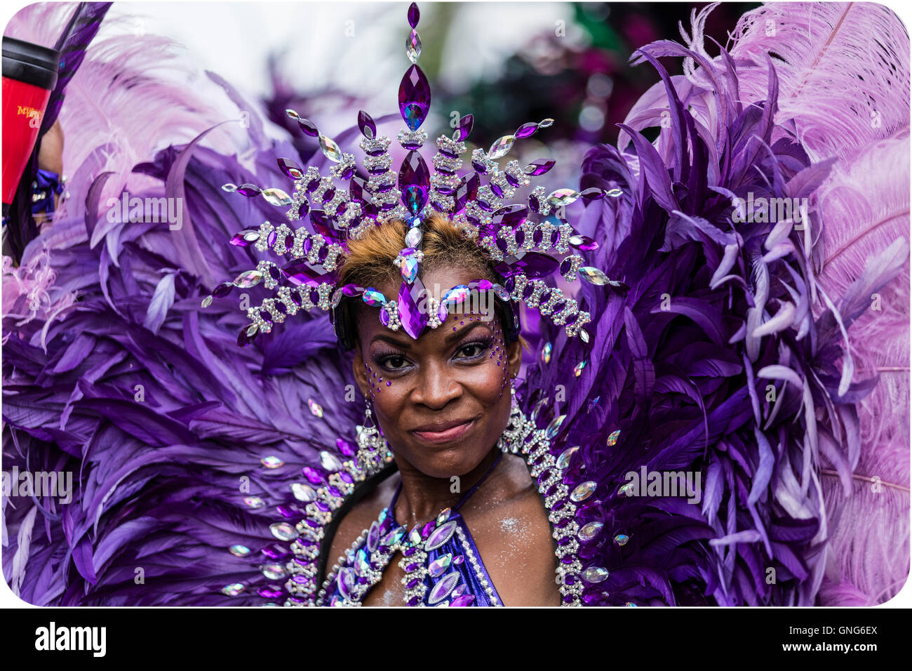 Beautiful Afro Caribbean woman in costume at the Notting Hill Carnival in West London in purple feathers - Stock Image