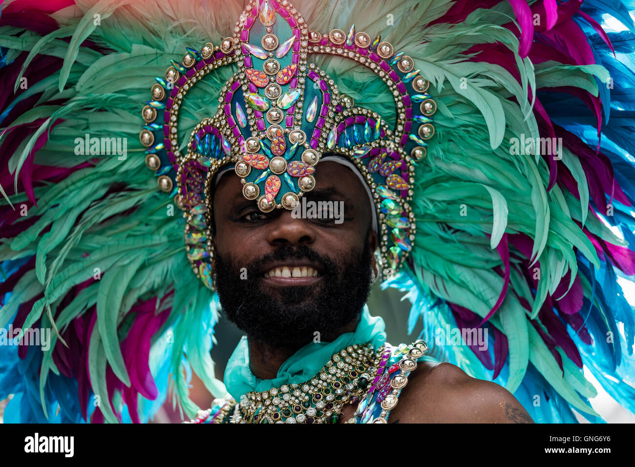 Black African looking man dressed in bright green feathers and headdress for the Notting Hill Carnival - Stock Image