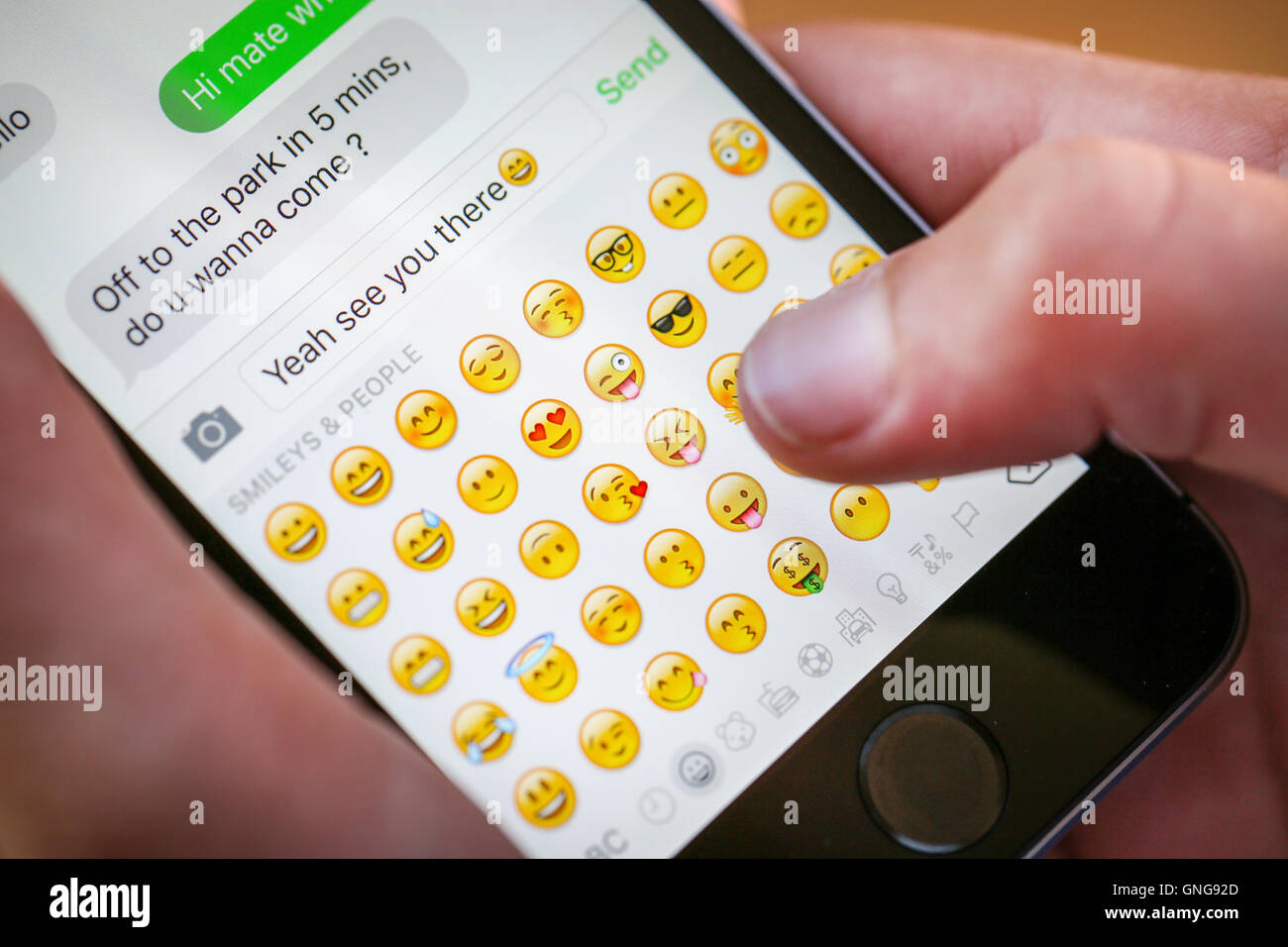 A teenage boy using an emoji whilst texting on his iphone - Stock Image