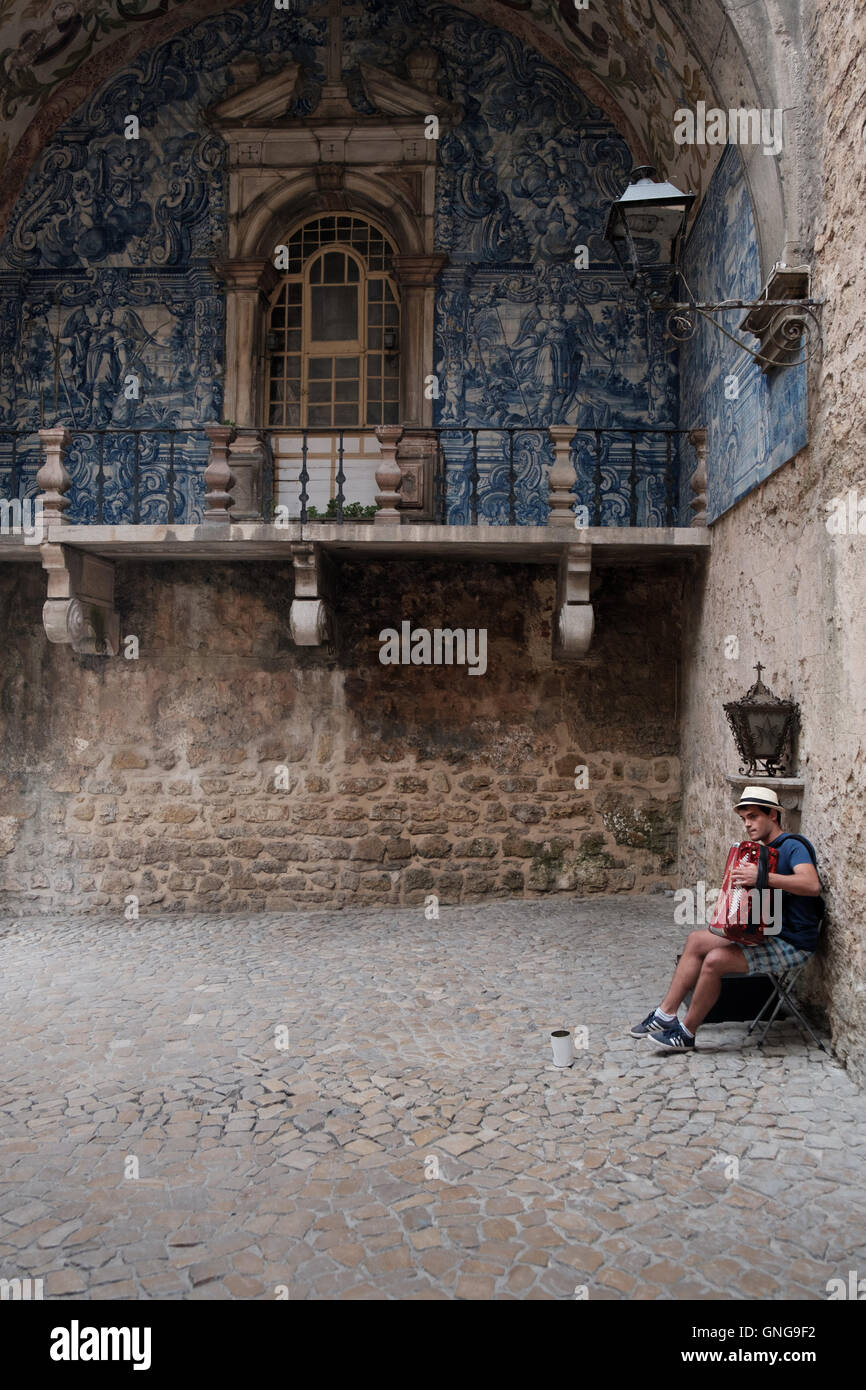 A street performer plays his accordion and sings in the city gate of Obidos, Portugal. - Stock Image