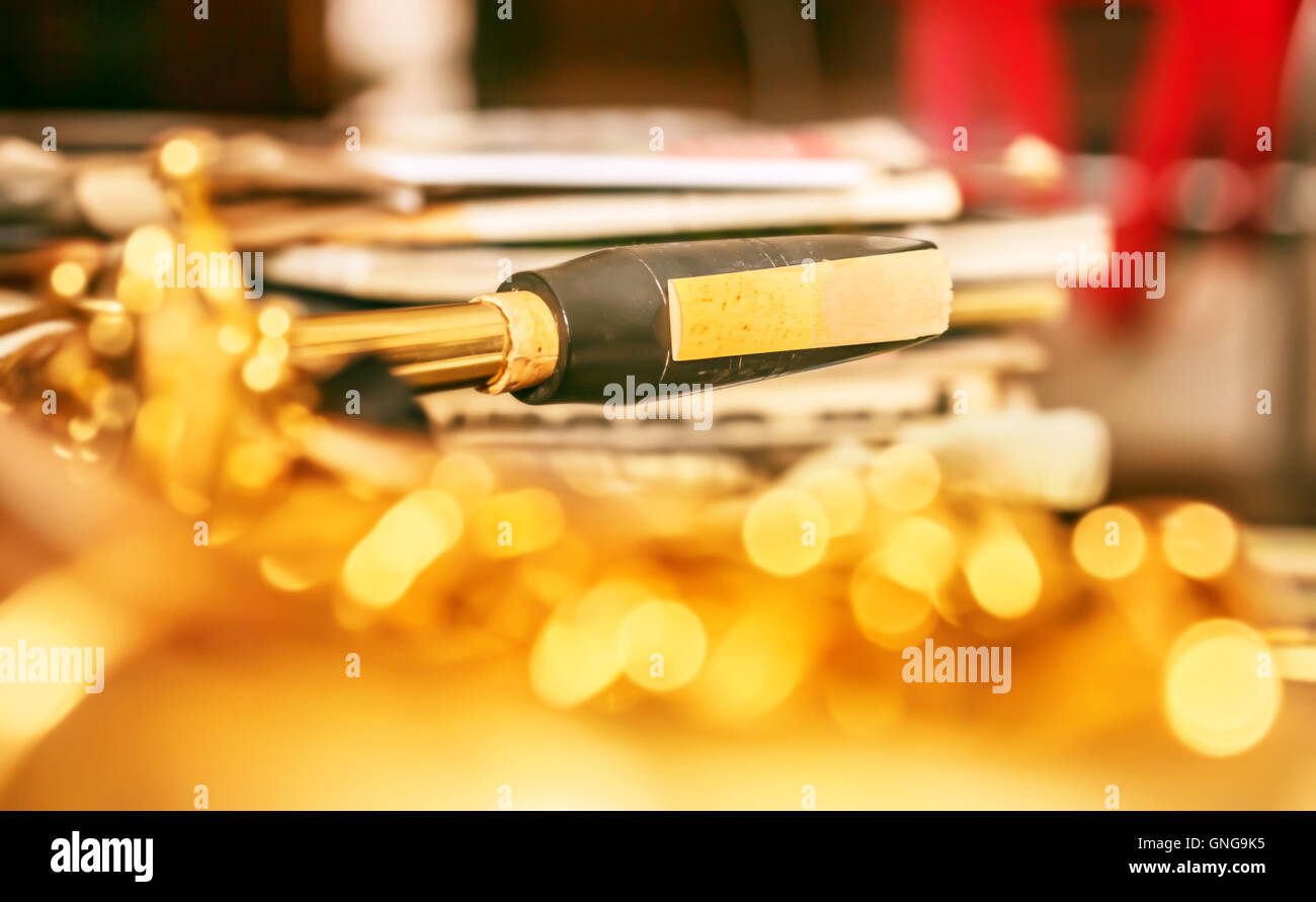 Detail of sax mouthpiece in bright golden background - Stock Image