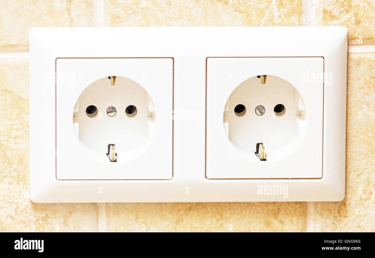 Two white sockets in light beige wall - Stock Image