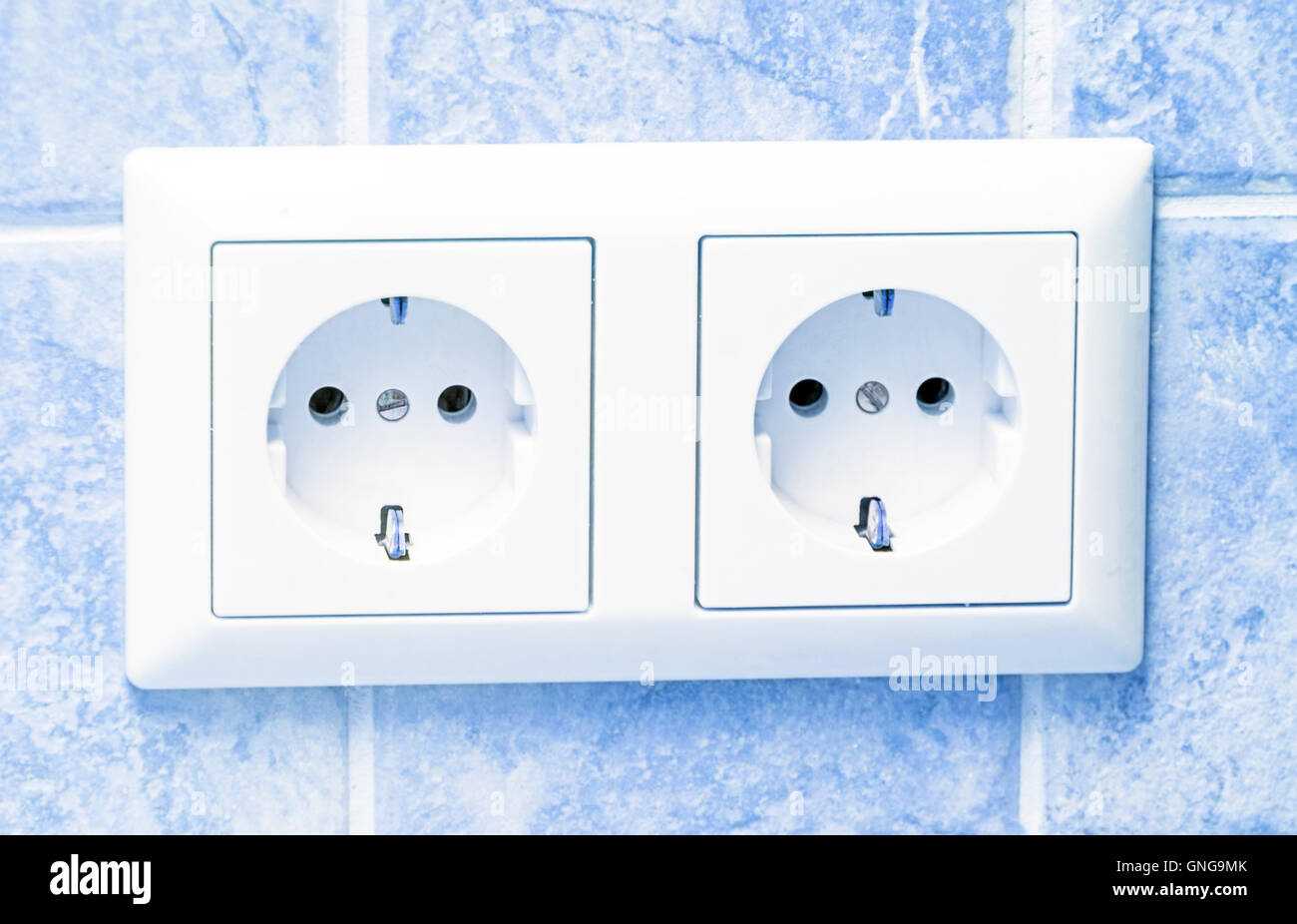 Two white sockets in light blue wall - Stock Image
