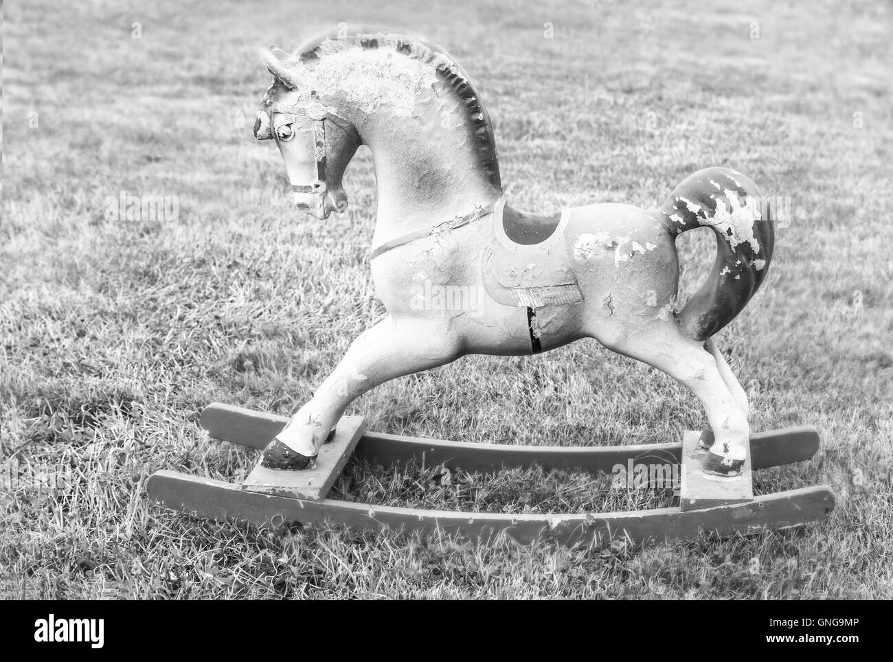 Nice vintage rocking horse on summer grass in black and white colours - Stock Image