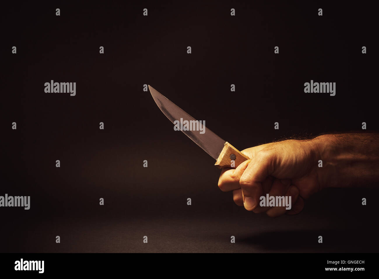 Conceptual composition of a dangerous situation, somebody is holding a knife. - Stock Image