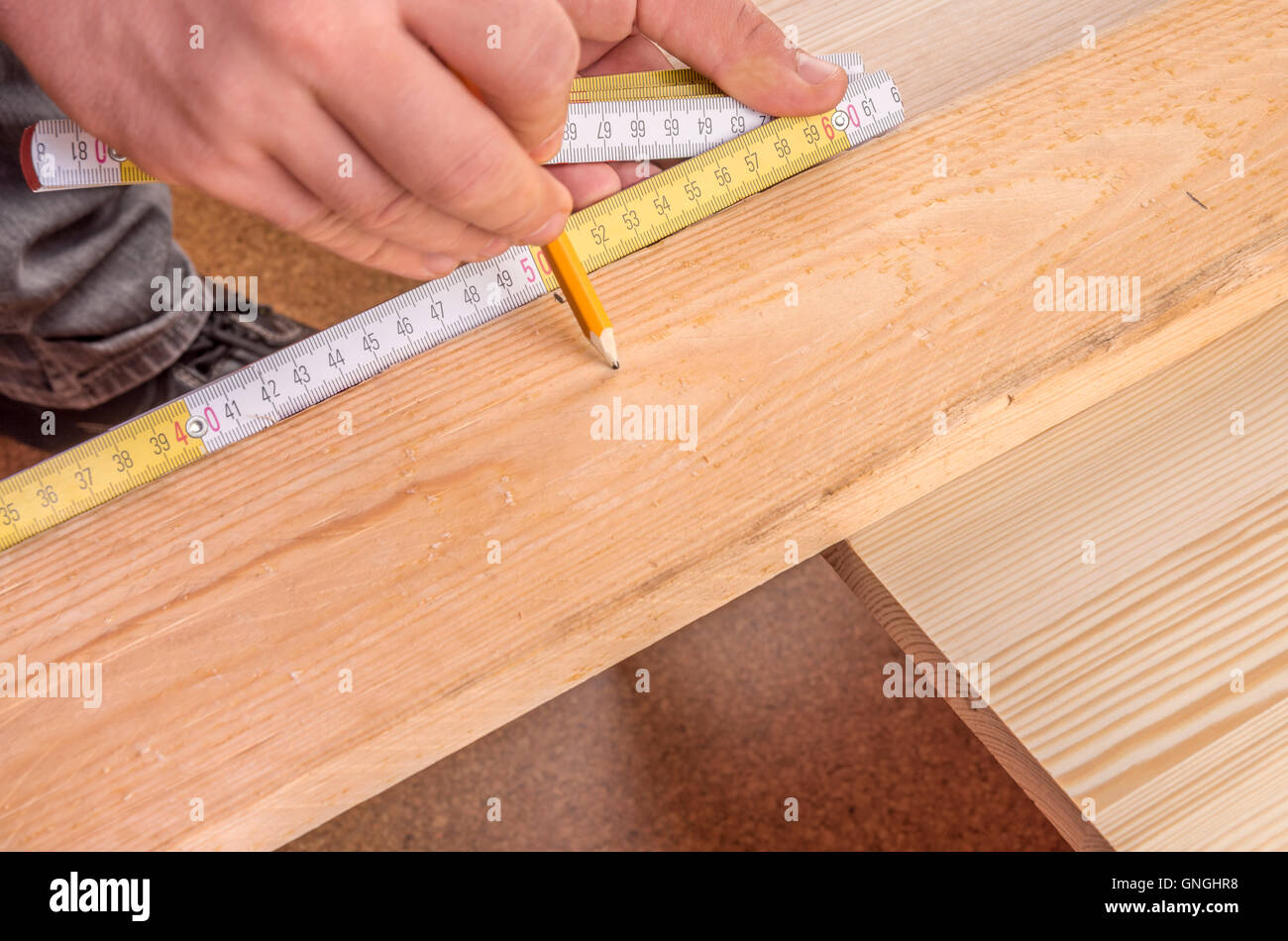Carpenter's hands measuring a wooden board - Stock Image