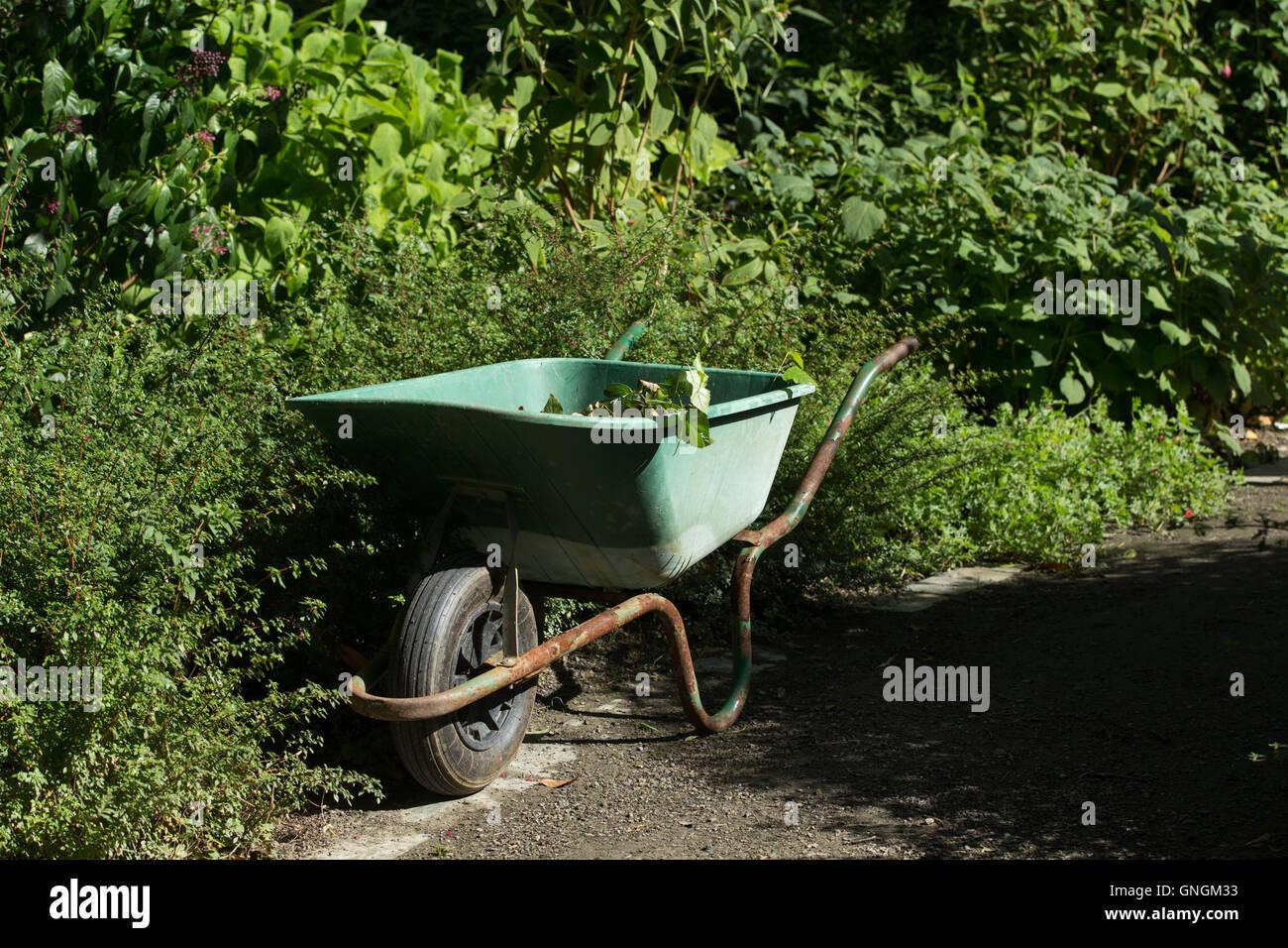 A gardeners best friend - a wheelbarrow on a garden path beside a flower border - Stock Image