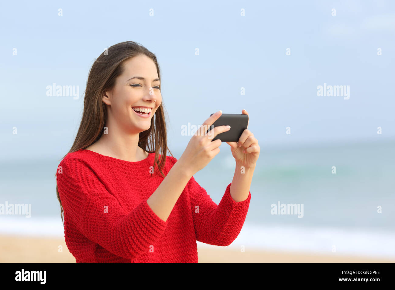 Portrait of a happy girl wearing red sweater laughing while watching streaming videos in smart phone on the beach - Stock Image