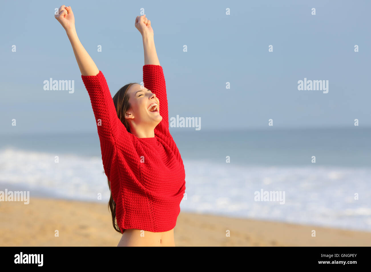 Happy funny excited woman wearing red color sweater raising arms euphoric on the beach at sunset with a warm light - Stock Image