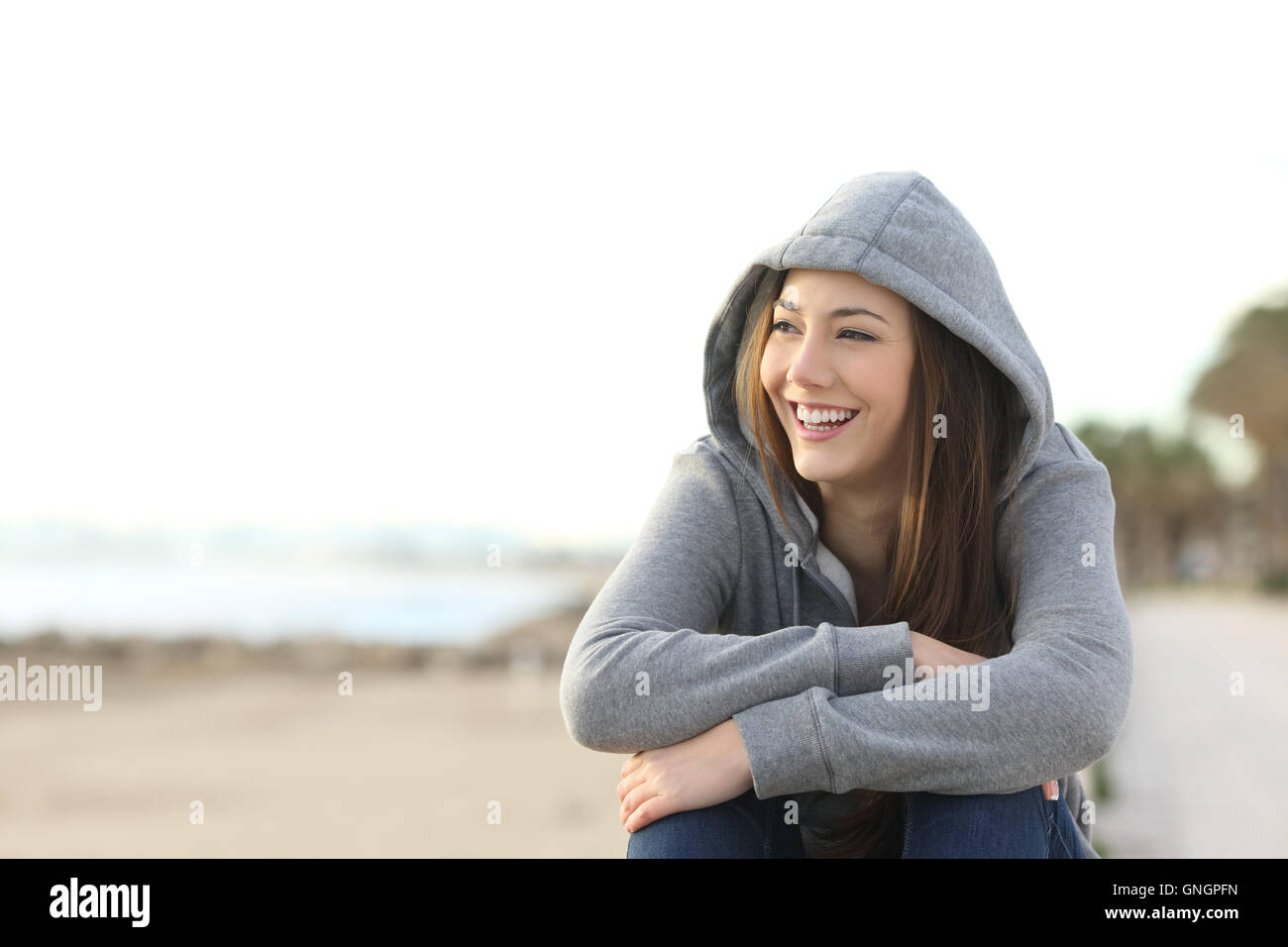 Portrait of a happy teenager girl smiling and looking at side outside on the beach - Stock Image