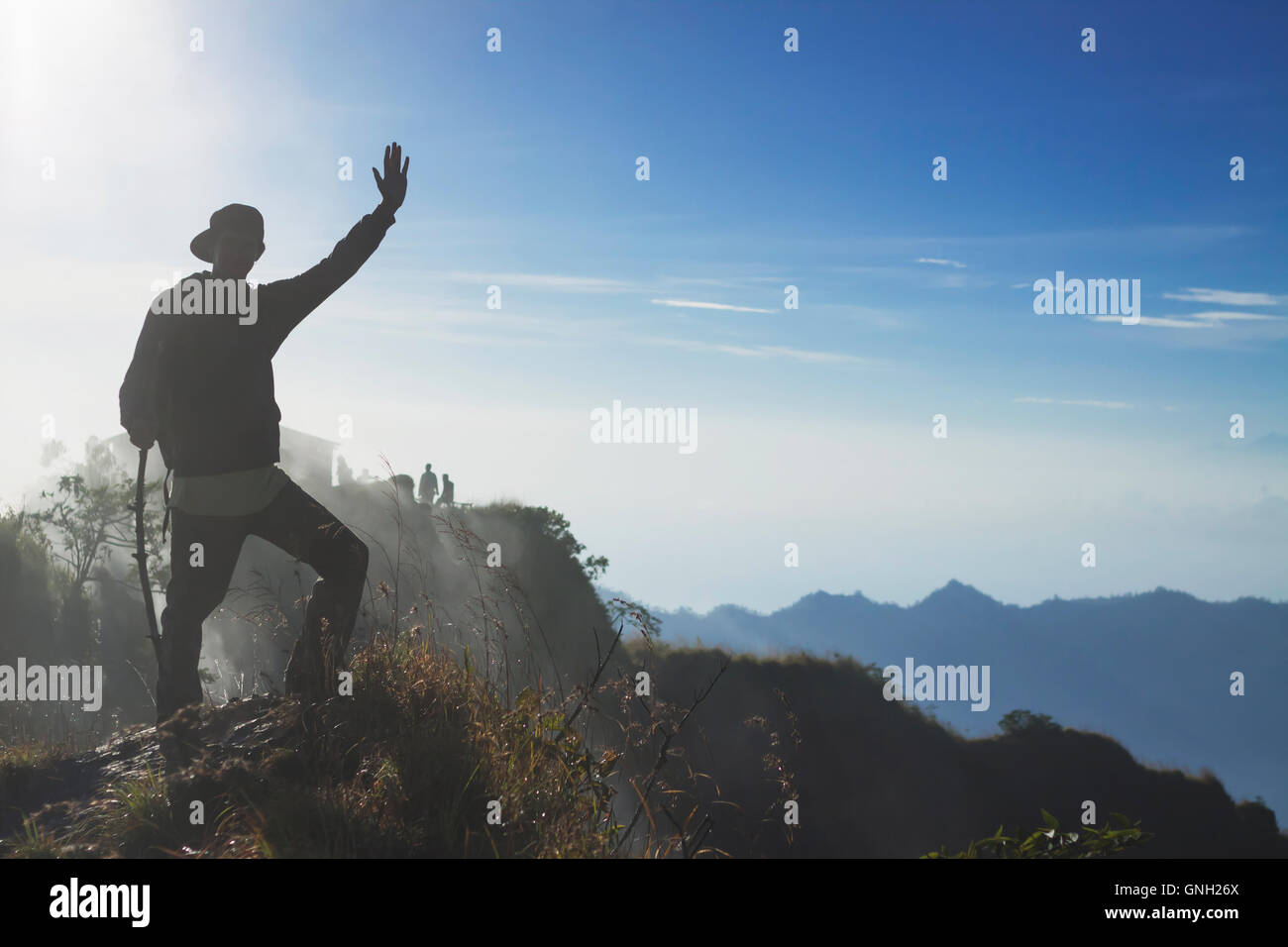 Silhouette of a man standing on mountain waving, Mount Batur, Bali, Indonesia - Stock Image