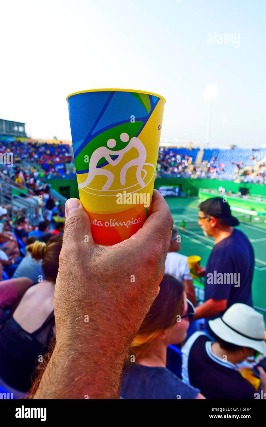 Hand holding an Olympic tumbler depicting wresting . These were given with Skol beer inside the Rio Olympic venues - Stock Image