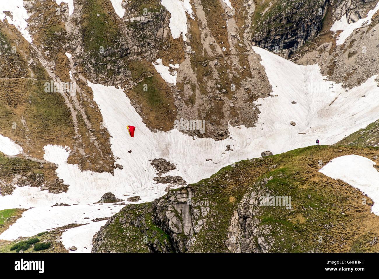 hiker and Paraglider in the Allgäu Alps near Oberstdorf, Oberallgäu, Bavaria, Germany Stock Photo