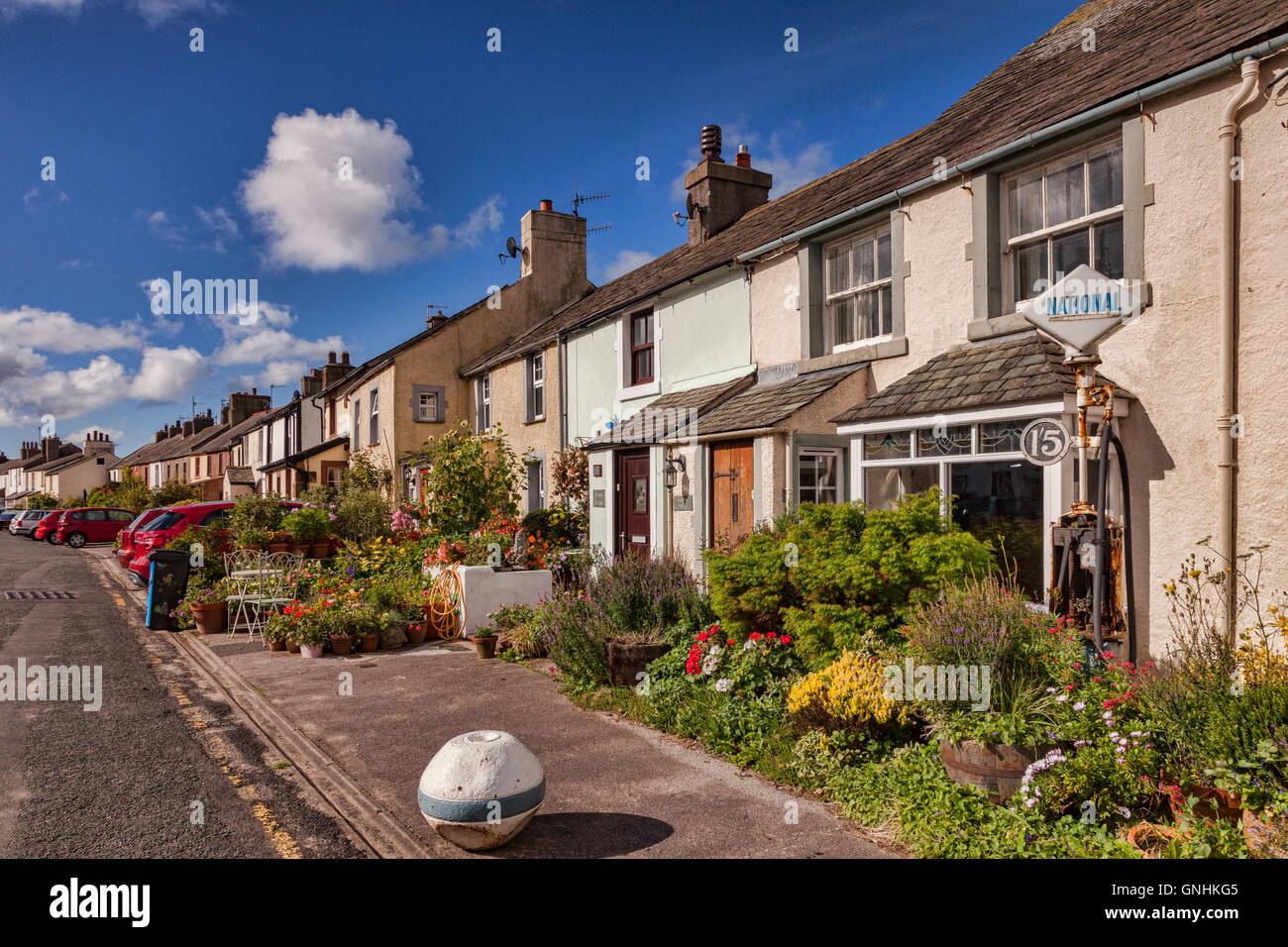 Row of cottages with lovely summer gardens in Main Street, Ravenglass, Cumbria, England, UK - Stock Image
