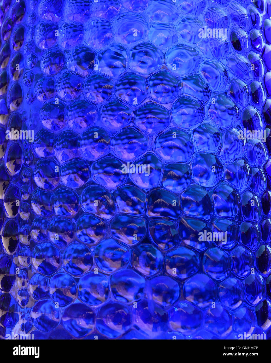 Dotted dark blue glass for backgrounds. Bubbly blue glass like liquid. - Stock Image