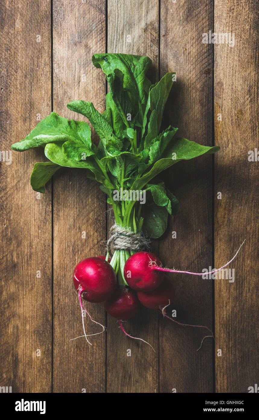 Fresh radish bunch over wooden background, top view, vertical composition - Stock Image