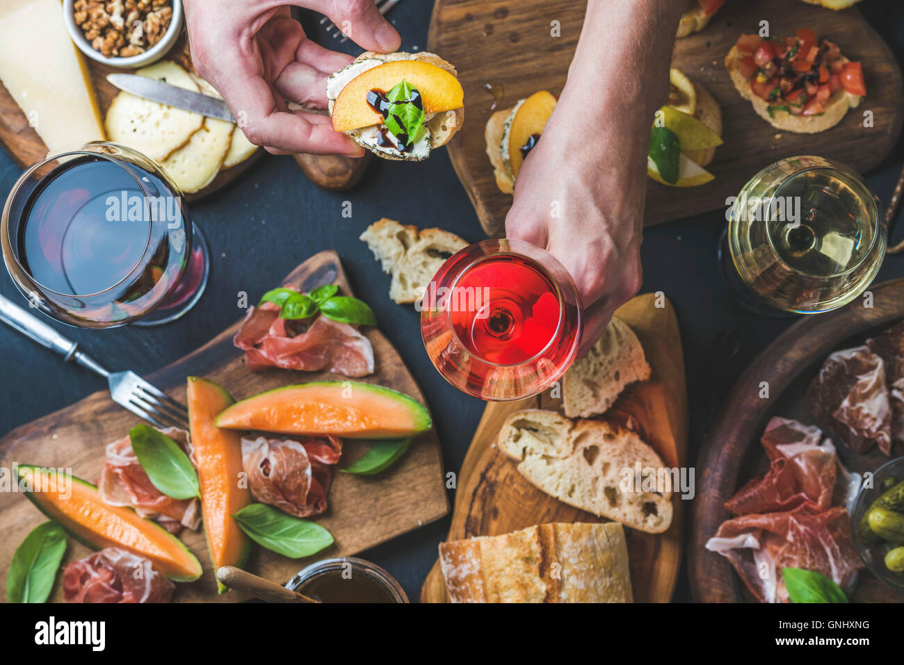 Italian wine antipasti snack variety and man's hands holding glass of rose wine and bruschetta, top view, selective - Stock Image
