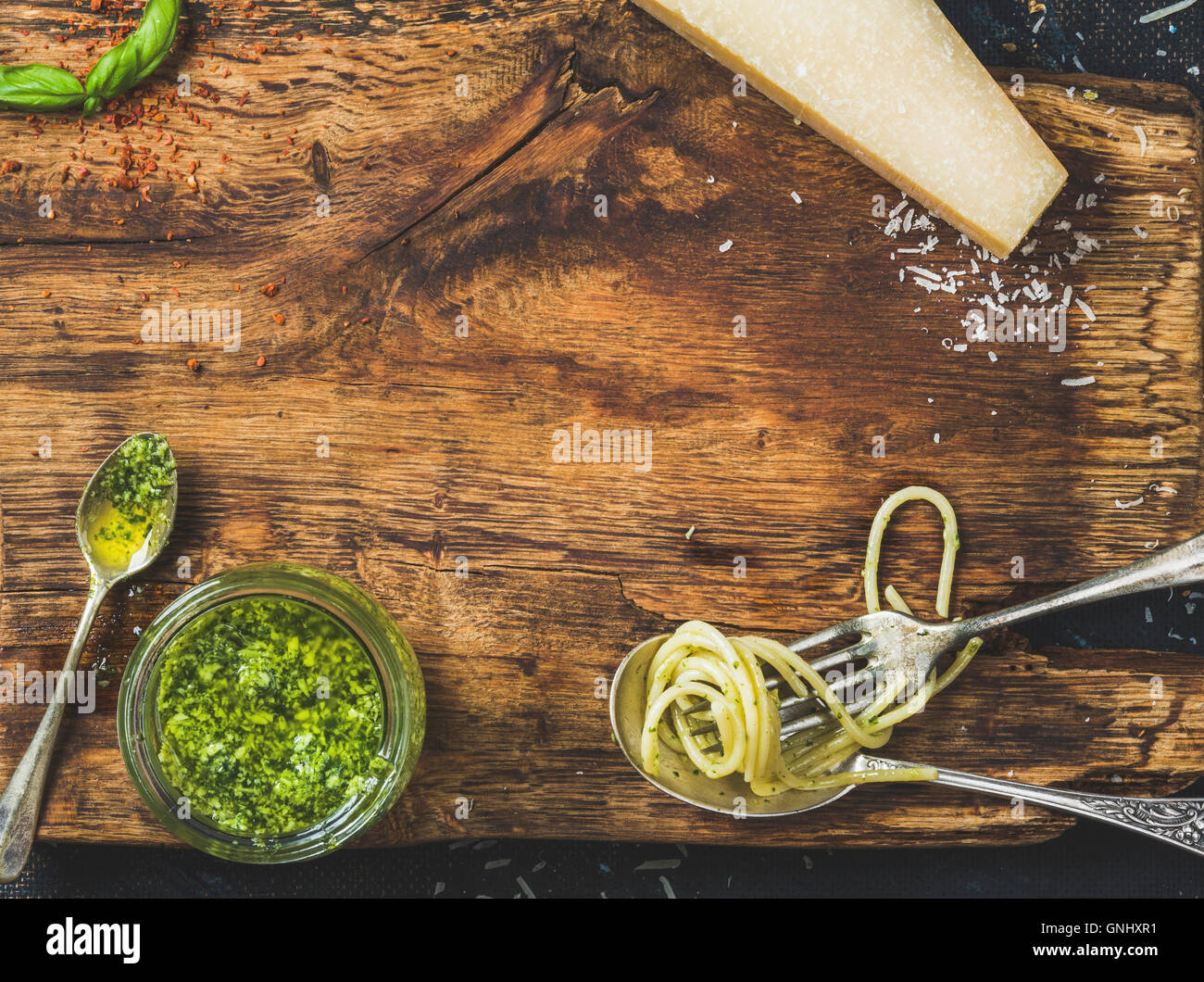 Italian cuisine cooking background. Jar with pesto sauce, spoon and fork with cooked spaghetti, fresh basil leaves - Stock Image