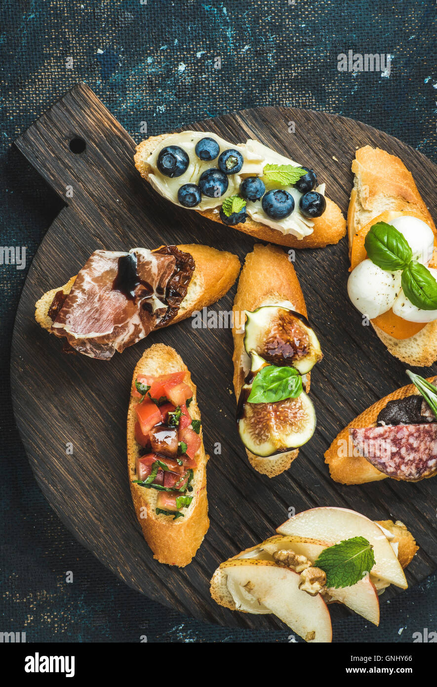 Italian crostini with various toppings on round wooden serving board over black plywood background, top view - Stock Image