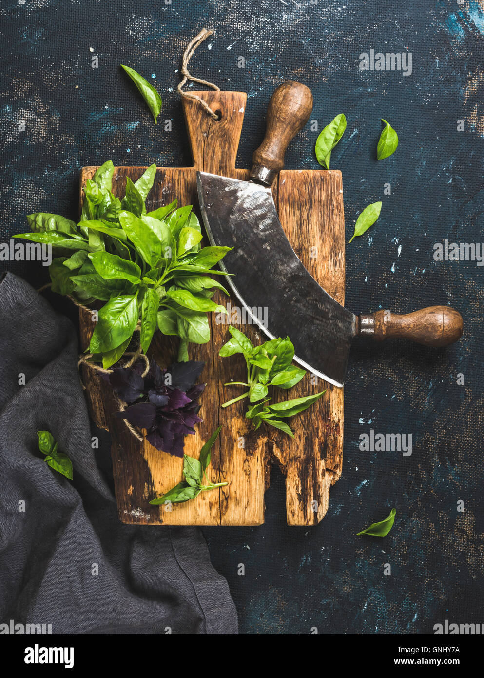 Fresh green and purple basil leaves with herb chopper knife on rustic cutting board over grunge dark blue plywood - Stock Image